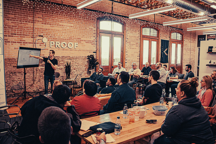 Ein Mann präsentiert einen Vortrag auf einem Bildschirm während eine Gruppe von Menschen im zuhört