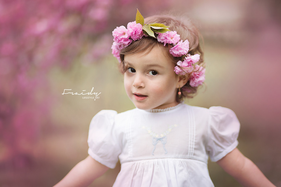 Little girl with  cherry blossom DIY hair wreath and Feltman Brothers White Dress during a cherry blossom spring photoshoot in Monsey, NY by Top NY photographer Fraidy Shimon of Peppermint Photography