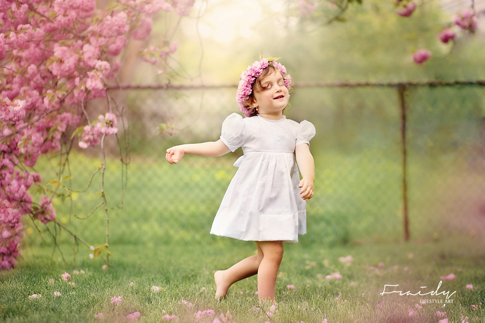Little Girl in white dress dancing during a cherry blossom photoshoot in Monsey, NY by Top NY Photographer Fraidy Shimon of Peppermint Photography