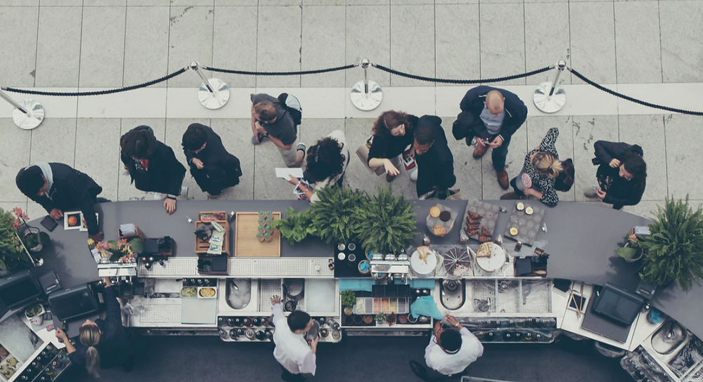 A birds eye view of people queuing outside a coffee shop