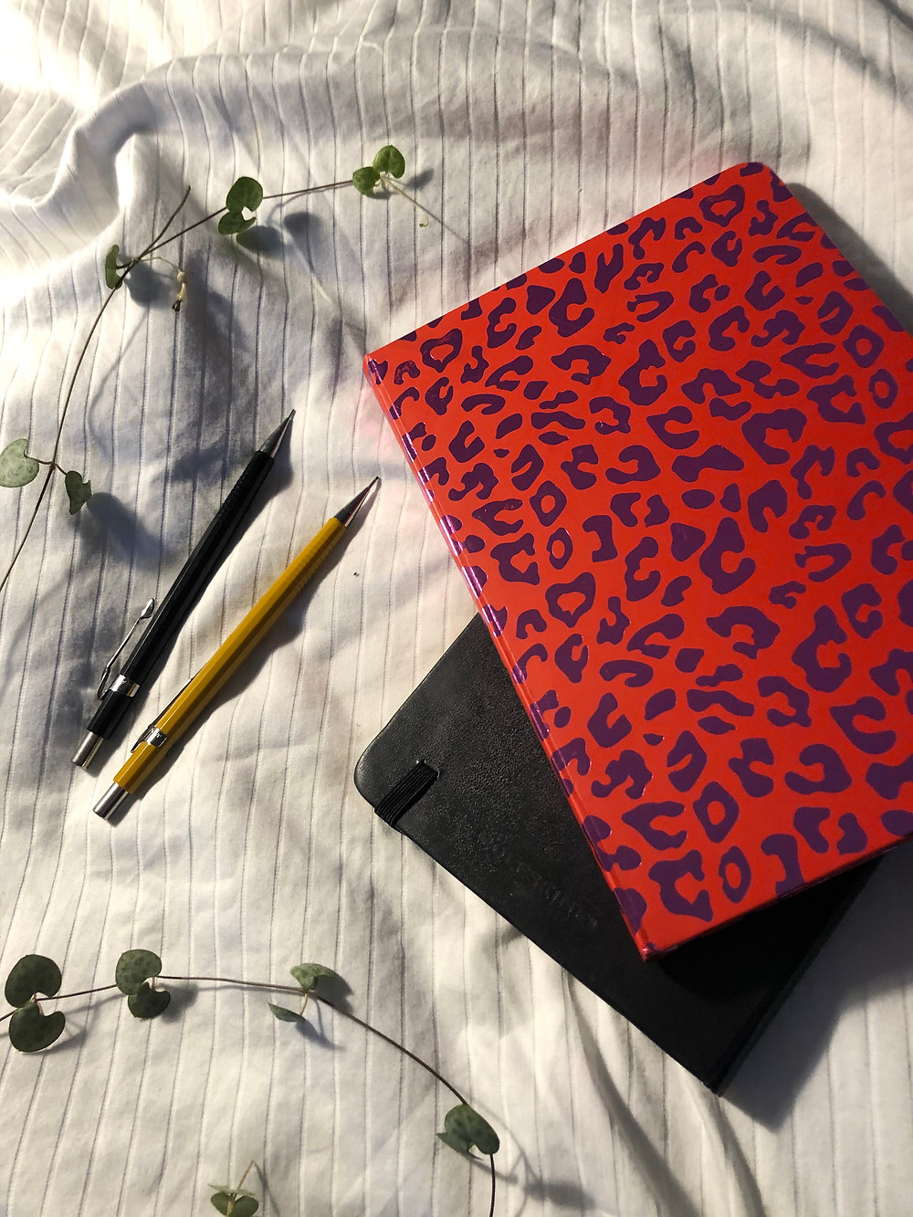 A red leopard print diary and a pencil on a white sheet