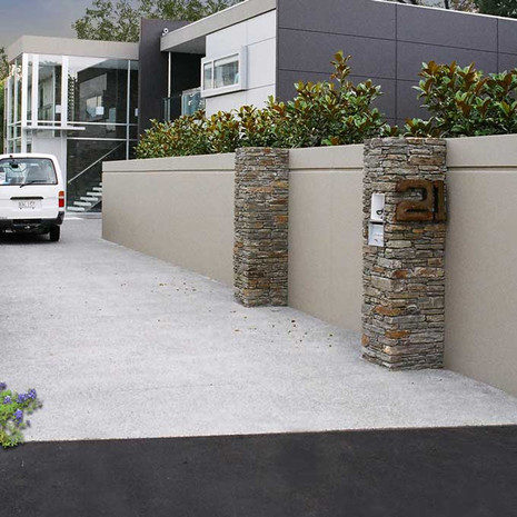 Guide your car into the driveway with a sleek wall design that simultaneously separates your private living space from the more public aspects of your home.