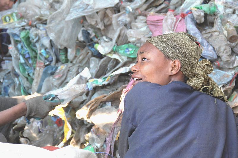 Una donna che lavora la plastica PET in un centro di riciclo