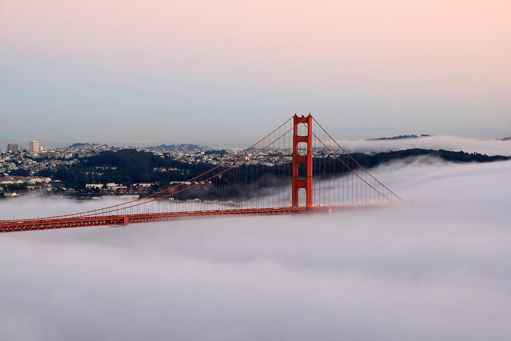 the South tower of the Golden Gate Bridge in San Francisco, CA, emerging from fog at sunset.