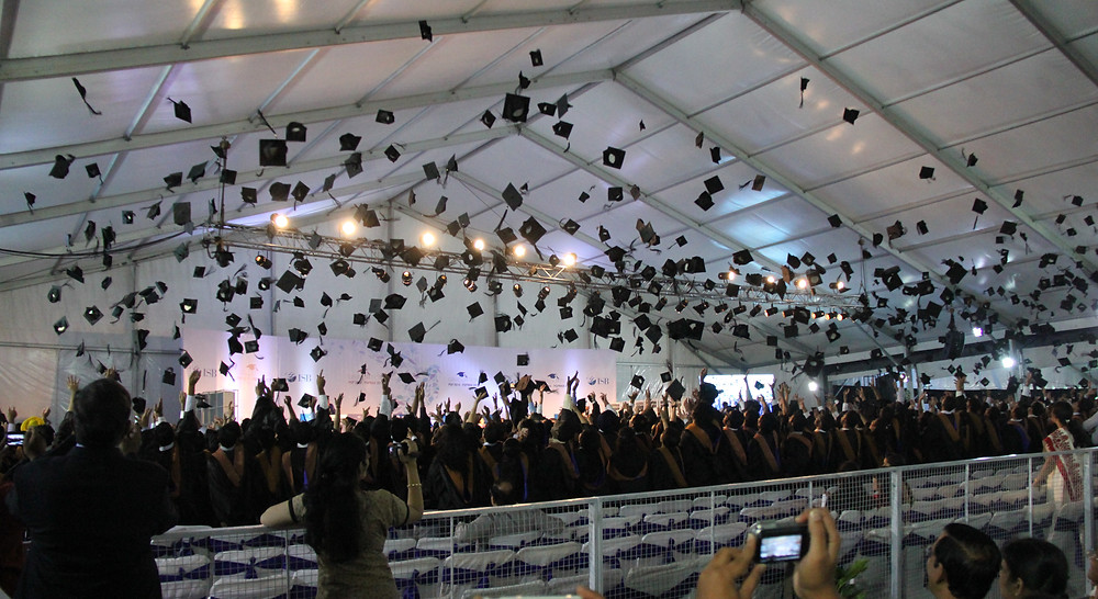 Square academic cap being tossed in air by fresh graduates