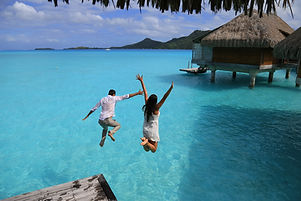 Happiness jump of young couple on the wa