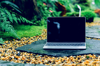 Laptop%2520computer%2520mockup%2520has%2520empty%2520screen%2520outside%2520on%2520stone%2520in%2520
