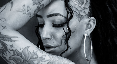 Woman with tattoos, big hoop earings, black and white imae