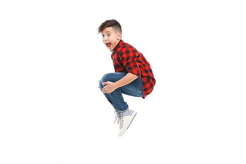 Side view of excited young boy jumping i