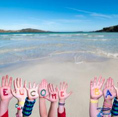 Children Hands Building Word Welcome Back, Ocean Background.jpg