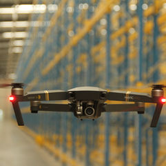 Drone flight inside a logistic centre. Commercial warehouse.