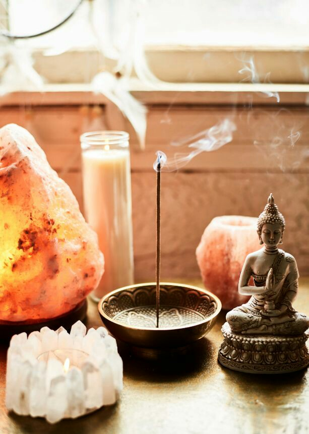 Incense, candles and a serene deity or image.