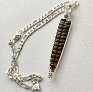 Rattlesnake tail set in Sterling Silver with a Sapphire