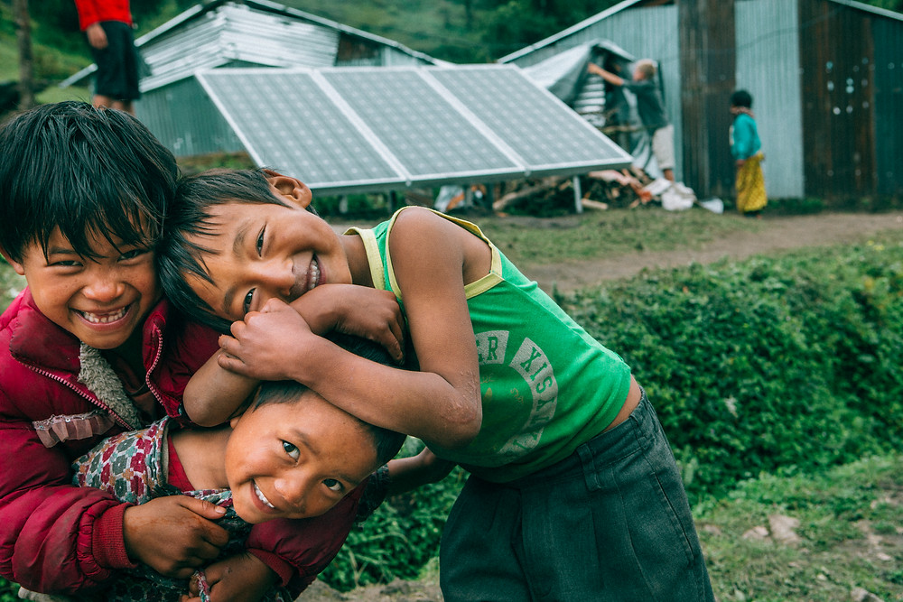 Three kids aged 4-5 stand in front of a small solar panel array in a village in Nepal. They hug each other while smiling for the camera. Image courtesy of the GivePower foundation.