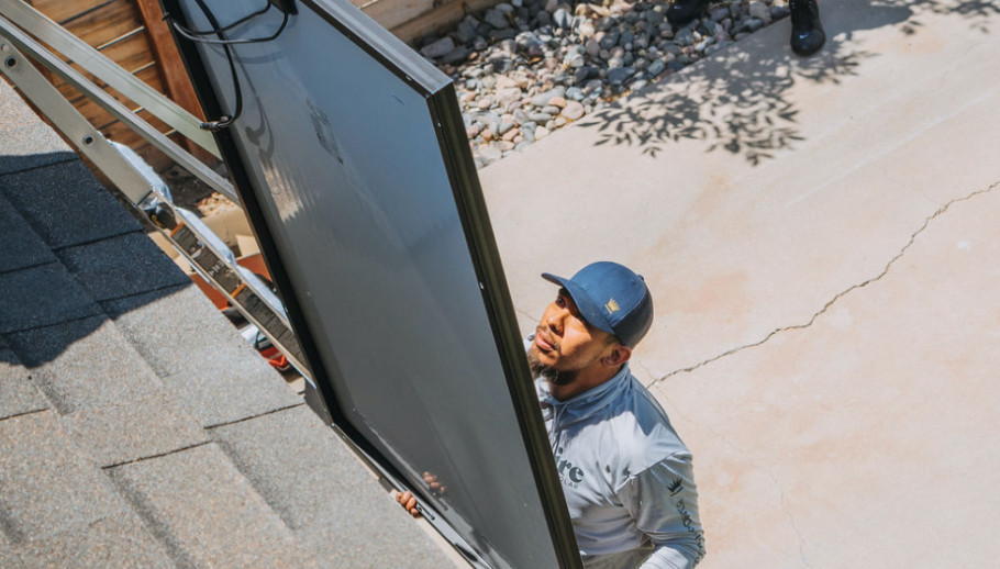 POV from the rooftop looking down at a solar installer lifts up a grey and black panel to the roof.