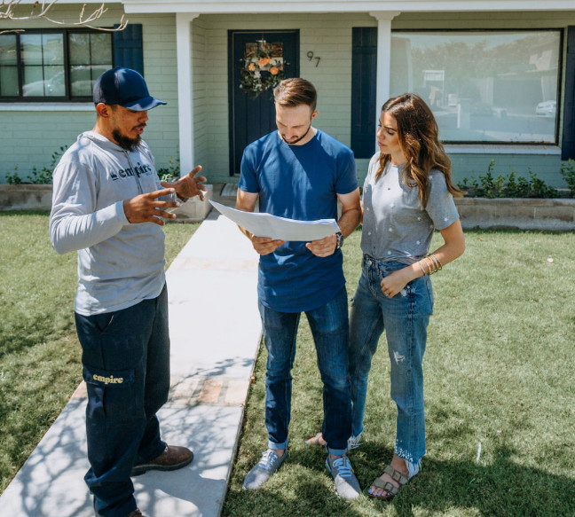 A solar installer wearing a grey Empire hoodie stands next to a young couple looking at solar panel layout blueprints in front of their house. The installer holds his hands up as if he's explaining how the pieces fit together, and the couple looks focused on the designs.