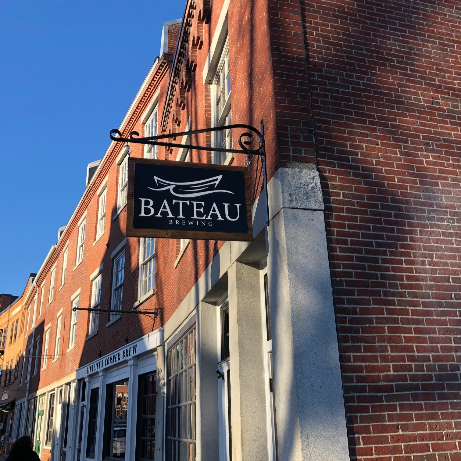 """Row of brick buildings with a hanging sign reading """"Bateau Brewing"""""""