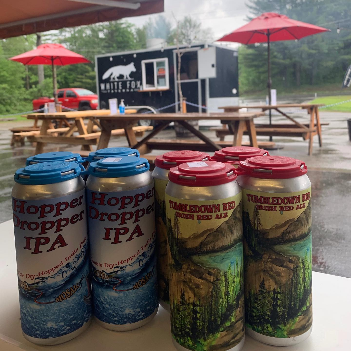 Two 4-packs of beer cans in front of a patio with wood picnic tables and a food truck called White Fox.