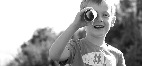 Junge blickt durch ein Fernrohr.
