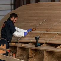 boat builders carefully install the tongue-and-groove fir planks that form the hull's inner core