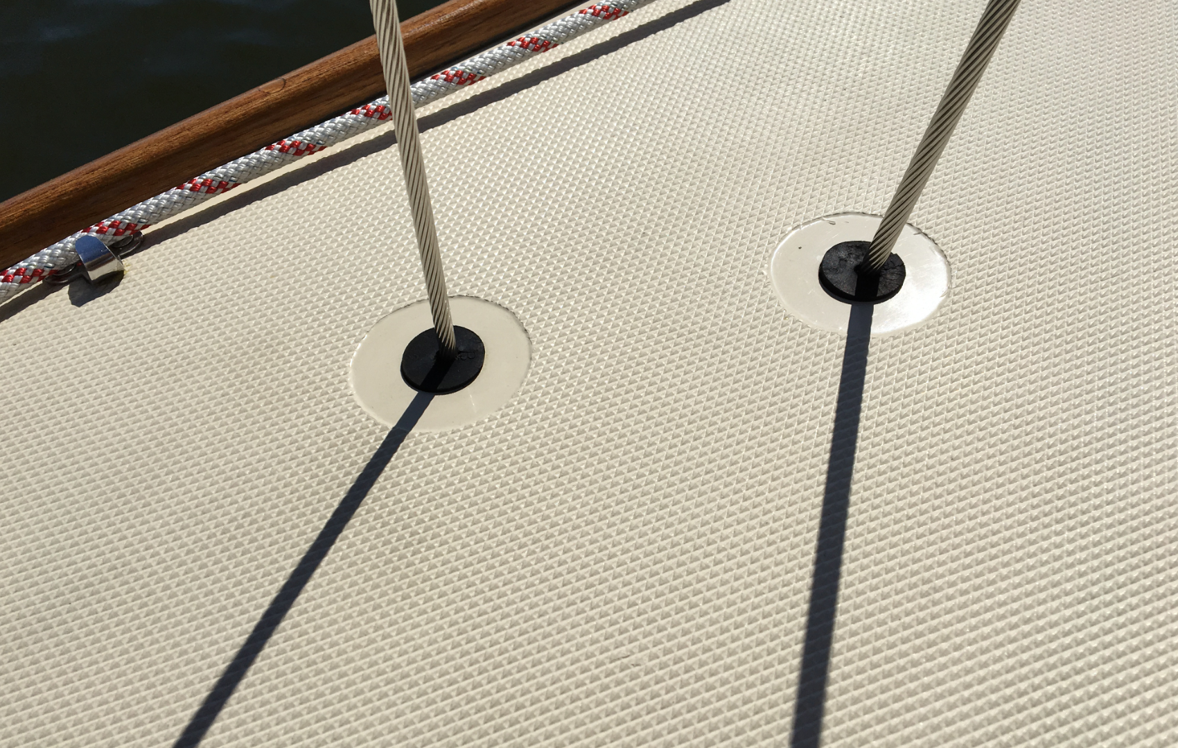 Wire rigging entering deck and going below to turnbuckles.