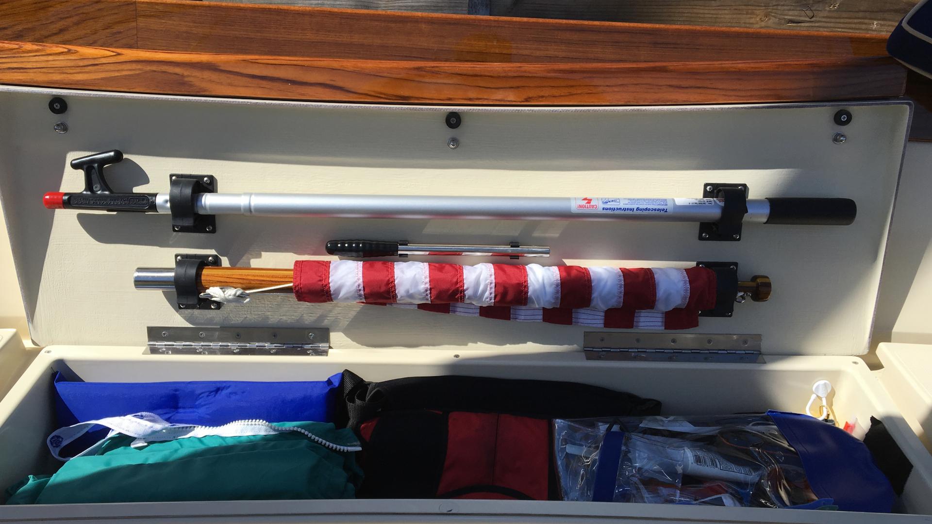 Starboard cockpit locker showing standard placement of boat hook, manual bilge pump handle and ensign pole.