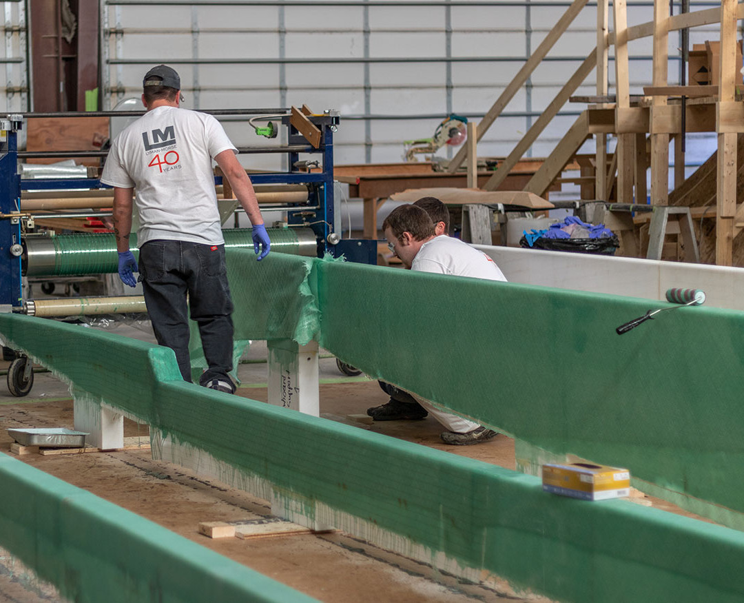 Simultaneously, a team is laminating the longitudinal stringers that will later be placed into the construction jig.