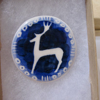 Sutton Hoo: The wet stone with the stag standing on top, this is a representational design in blue.