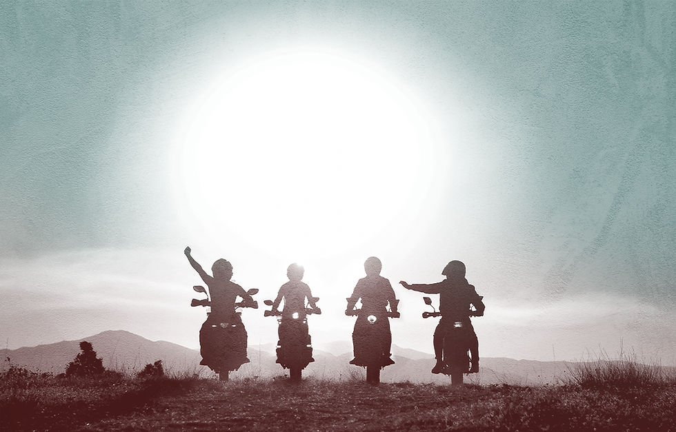 Four motorcyclists riding toward the sunset, one of them raising her arm in victory.