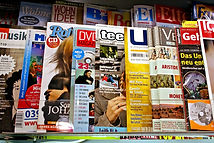 Lots of magazines overlapping on a shelf.