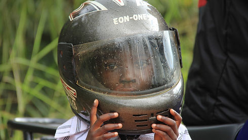 little boy with helmet on motorbike in Africa; Save Money, go Green and Connect with the Sun