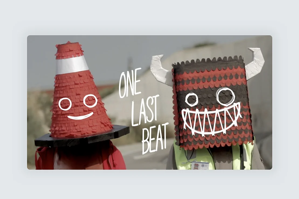 """A website screenshot showing two masked people with the lettering """"One Last Beat"""""""