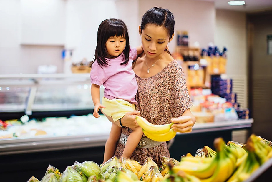 A stock photo of a mother and child shopping for groceries.