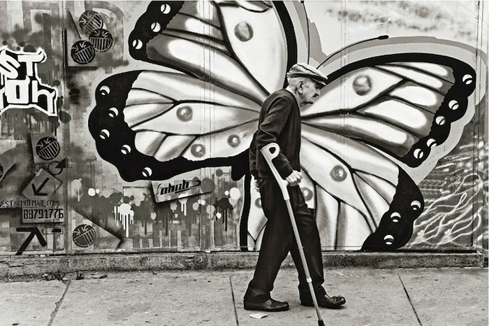 Elderly man with in front of graffiti with butterfly wings