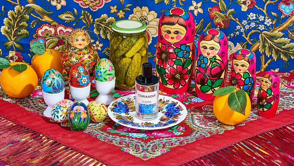 A photo of matryoshka dolls, a jar of pickles, decorative eggs and oranges surrounding a D.S. & Durga perfume bottle, by Wade and Leta