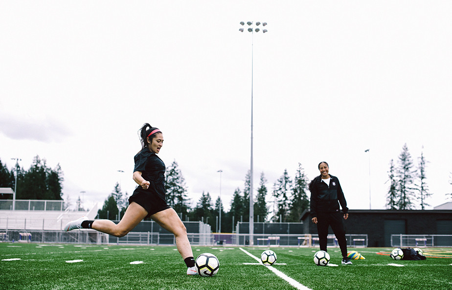 Two women playing soccer by TONL.