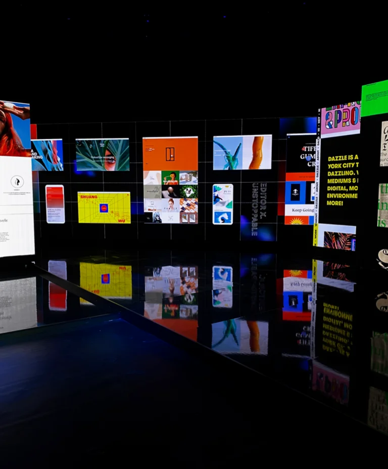A photo of the Editor X Unstoppable event stage, showing many user websites on large screens.