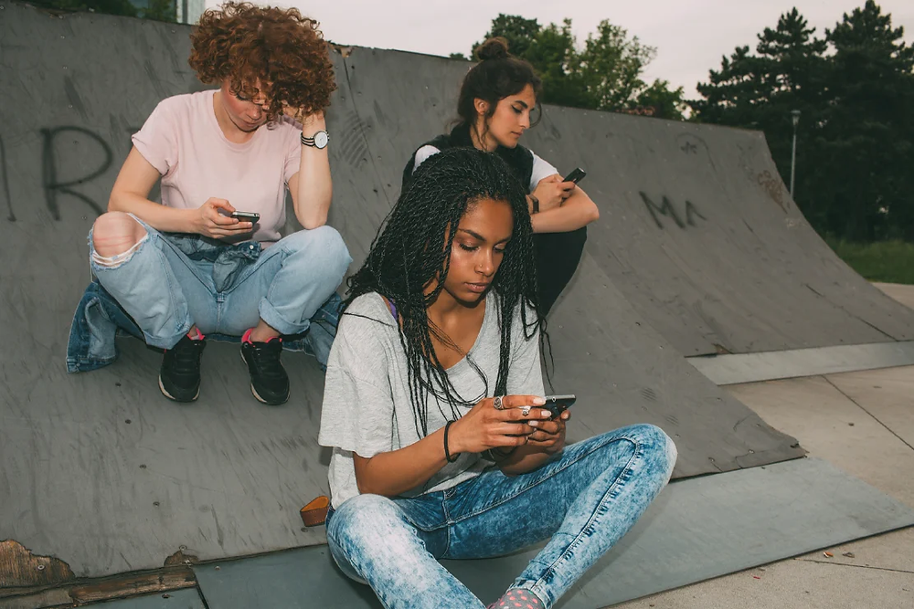 Three young women interacting with their mobile phones outdoors