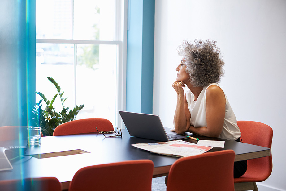 Middle-aged woman looking out of the window in the boardroom.