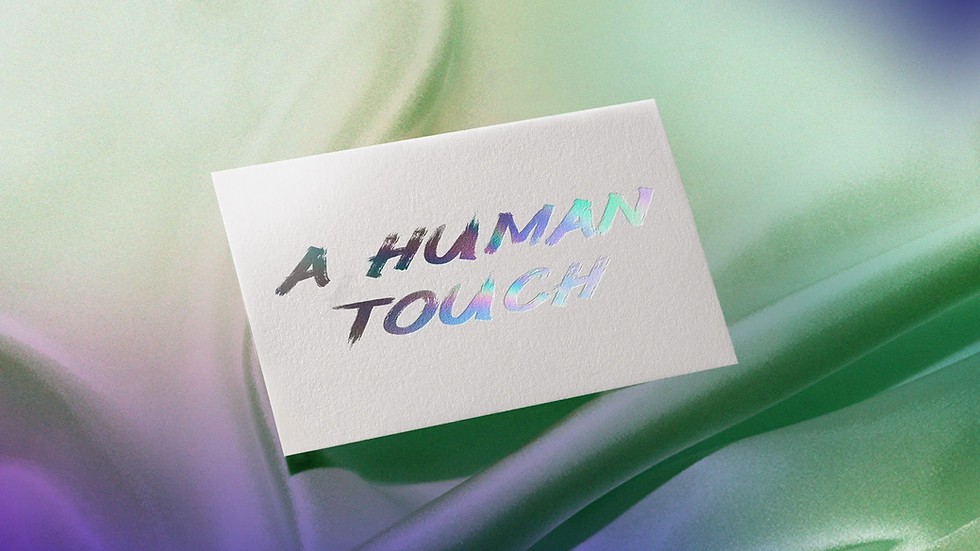 """A paper note with the text """"A human touch"""" printed on it in metallic foil, in a handwriting font, placed against a fabric background"""