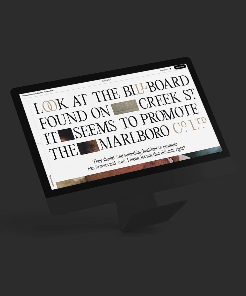 A computer showing the Editorial New website design by Locomotive, with large serif typography filling the screen.