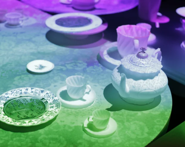 A photo of a table set with white ceramic dishes, lit with 3D projection mapping