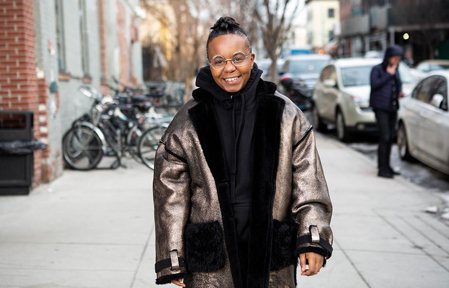A transmasculine person in a winter coat on the sidewalk.