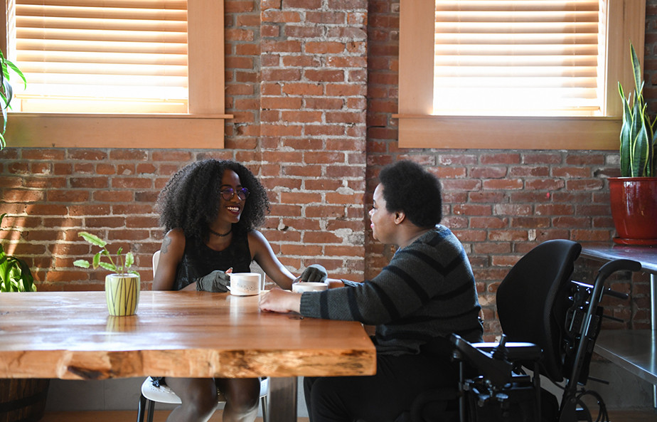 Two disabled Black women in a coffee shop.