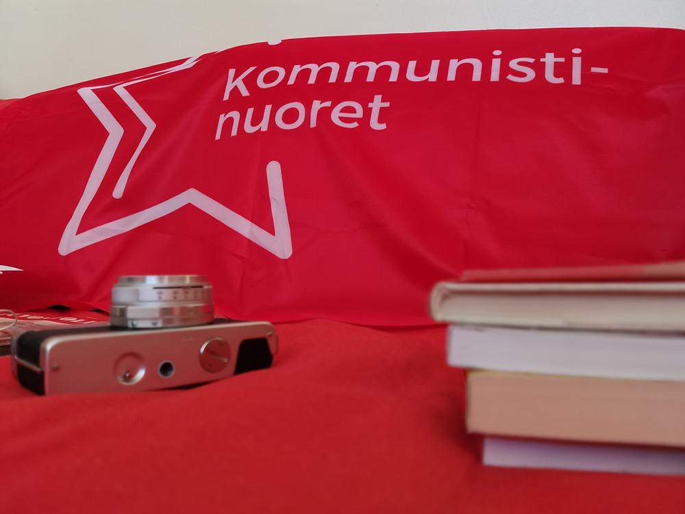 Kuvassa Kommunistinuorten punalippu, filmikamera ja teoriaa.