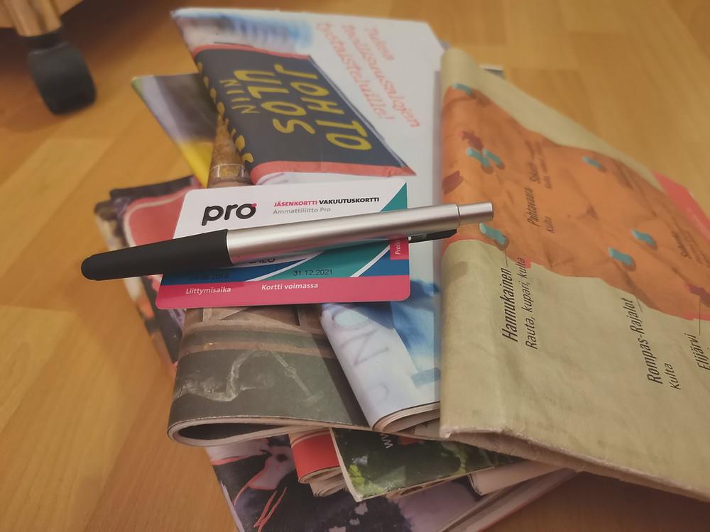 Työväenlehtiä pinossa ja pinon päällä Pron jäsenkortti ja kynä.
