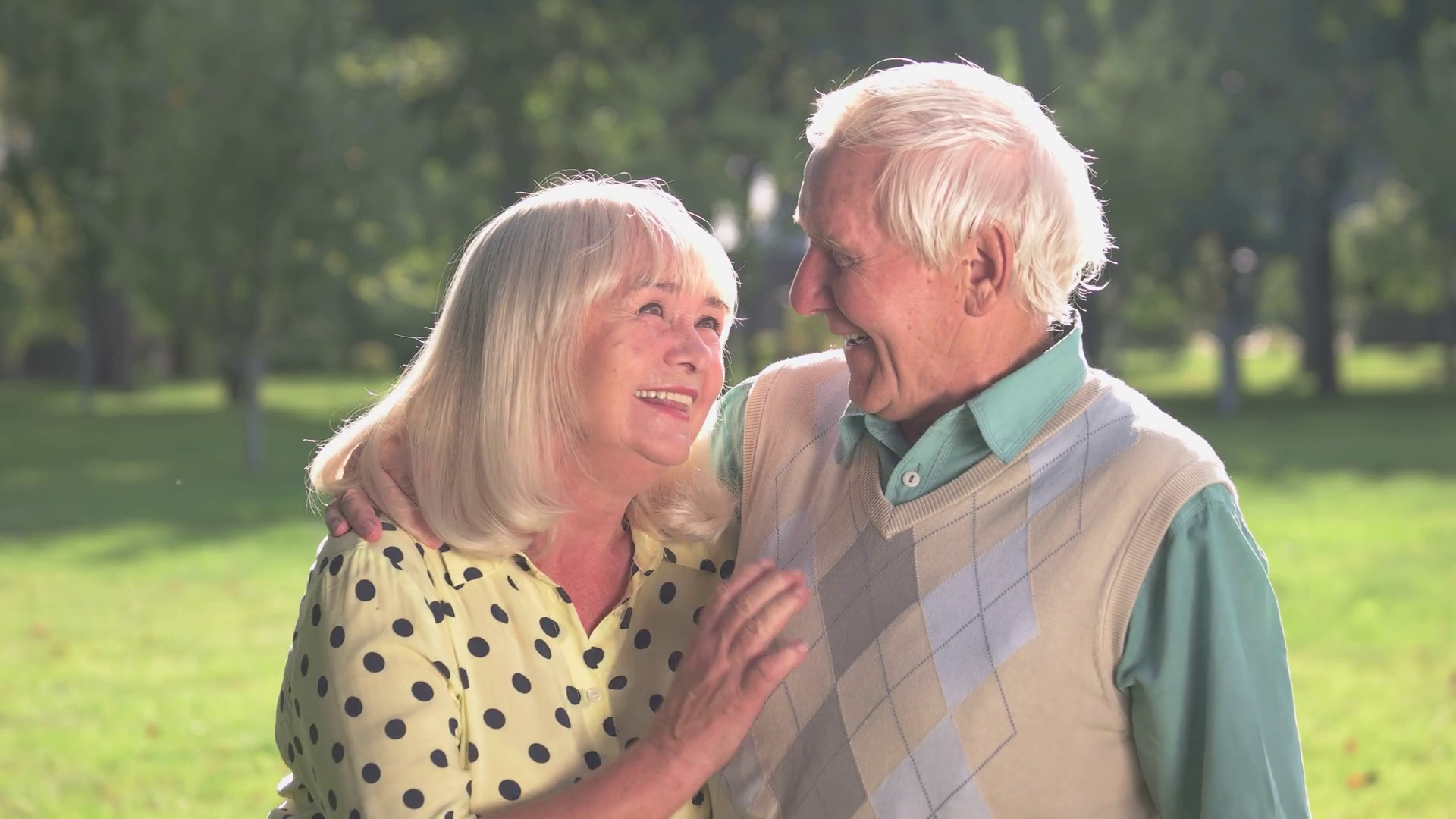 Retired couple looking at each other and smiling outside in park