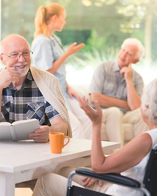 Seniors Gathered in a Common Area, Nurse talking with residents
