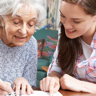 Volunteer helping resident with a crossword puzzle