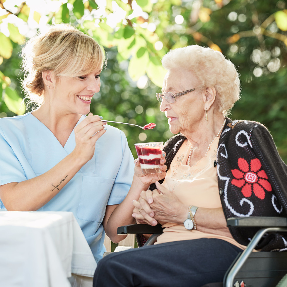 Care worker assisting resident to eat